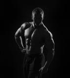 Homme musculaire sur le fond noir dans le studio Photographie stock