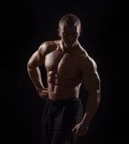 Homme musculaire sur le fond noir dans le studio Image libre de droits