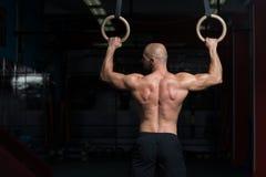 Homme musculaire tenant deux anneaux Images libres de droits