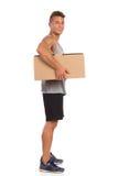 Homme musculaire tenant la boîte de carton sous son bras Images libres de droits