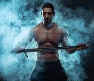 Homme musculeux sans chemise magnifique tenant une épée photo stock
