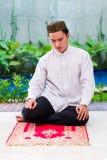Homme musulman asiatique priant sur le tapis image libre de droits