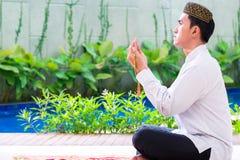 Homme musulman asiatique priant sur le tapis photo stock