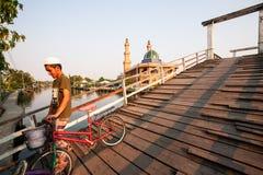 Homme musulman de sourire avec la bicyclette à travers le pont en bois au-dessus du Ca image libre de droits