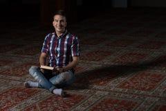 Homme musulman lisant le livre islamique saint Coran Image stock