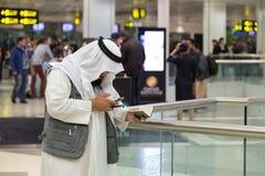 Homme musulman portant les vêtements traditionnels au bureau de renseignements chez Doha Photo libre de droits