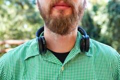 Homme mystérieux avec une barbe courte posant avec des écouteurs sur un fond naturel image stock