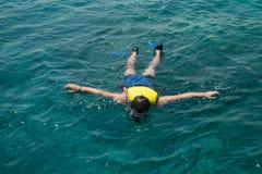 Homme naviguant au schnorchel dans l'eau avec le gilet de sauvetage Image libre de droits