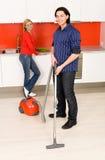 Homme nettoyant à l'aspirateur, femme à l'arrière-plan Images libres de droits