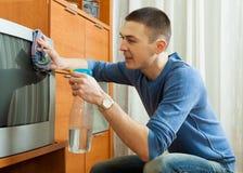 Homme nettoyant la TV Photographie stock libre de droits
