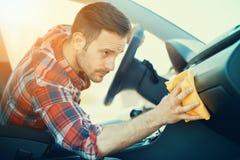 Homme nettoyant le tableau de bord de sa voiture Image libre de droits