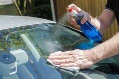 Homme nettoyant un pare-brise de voiture Photos libres de droits