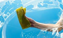 Homme nettoyant une fenêtre avec le tissu jaune Photographie stock libre de droits
