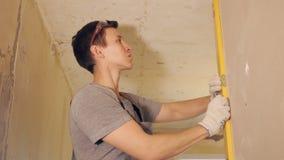 Homme nivelant le mur avec l'instrument clips vidéos