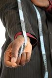 Homme noir d'affaires utilisant une bande de mesure photo libre de droits