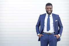 Homme noir sûr d'affaires dans une position élégante de costume contre le mur regardant la caméra avec l'espace de copie photo stock
