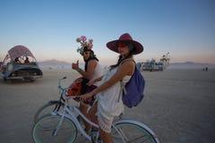 Homme non identifié et femme montant une bicyclette Image libre de droits