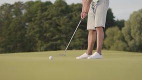 Homme non reconnu jouant au golf sur le champ de golf Homme sûr réchauffant et frappant la boule utilisant un club de golf E clips vidéos