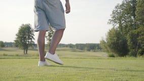 Homme non reconnu jouant au golf sur le champ de golf Homme sûr réchauffant et frappant la boule utilisant un club de golf E banque de vidéos