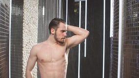 Homme nu détendant tout en ayant la douche obtenez l'énergie de l'eau Mouvement lent banque de vidéos