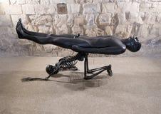 Homme nu de sculpture en bronze soutenu par le squelette d'agenouillement par Nino Longobardi dans une chambre de Castel Del Mont photographie stock libre de droits