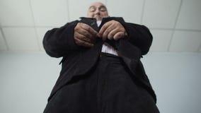 Homme obèse drôle dans le costume classique attachant un bouton sur sa veste, de poids excessif banque de vidéos