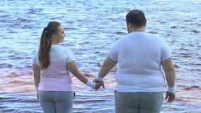 Homme obèse prenant à amies la main, couple appréciant la belle vue de la rivière clips vidéos