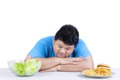 Homme obèse regardant la salade Photographie stock libre de droits