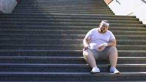 Homme obèse s'asseyant sur des escaliers pour se reposer pour la minute, épuisé après des séances d'entraînement banque de vidéos