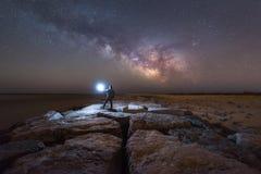 Homme observant la galaxie de manière laiteuse se lever d'une jetée Photo libre de droits