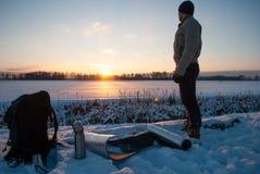 Homme observant le coucher du soleil le soir d'hiver, tourisme d'hiver, campant dans la neige, photos stock