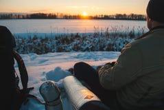 Homme observant le coucher du soleil le soir d'hiver, tourisme d'hiver, campant dans le plan rapproché de neige, photographie stock