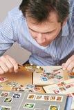 Homme observant une collection de timbres-poste photographie stock libre de droits