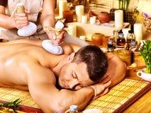 Homme obtenant des traitements de fines herbes de massage de boule. Image libre de droits