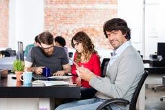 Homme occasionnel à l'aide du bureau fonctionnant se reposant de comprimé, gens d'affaires images stock