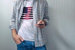 Homme occasionnel avec le drapeau des Etats-Unis sur la chemise utilisant le téléphone portable Images stock
