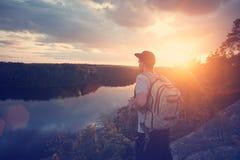 Homme occasionnel avec le sac à dos et le chapeau sur la falaise au-dessus de la rivière et du regard loin Photographie stock