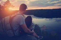 Homme occasionnel avec le sac à dos se reposant sur le bord de falaise au-dessus de la rivière et regardant loin Image stock