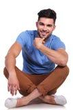 Homme occasionnel de sourire assis tenant son menton avec sa main photos stock