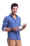 Homme occasionnel de sourire de jeunes tenant un comprimé de protection Image stock