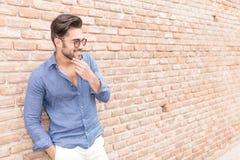 Homme occasionnel de sourire près de mur de briques s'interrogeant sur quelque chose Photos stock