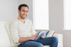 Homme occasionnel gai à l'aide de son comprimé Image stock