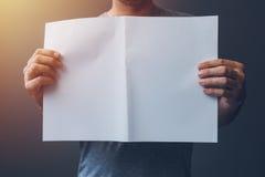 Homme occasionnel jugeant le papier A3 vide répandu comme espace de copie Photos libres de droits