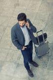 Homme occasionnel moderne d'affaires au téléphone portable dans l'aéroport de hall principal vi Image libre de droits