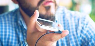 Homme occasionnel parlant au téléphone portable utilisant la reconnaissance vocale en café photos stock