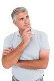 Homme occasionnel pensant avec la main sur le menton Photographie stock