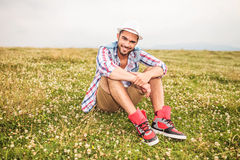 Homme occasionnel s'asseyant dans un domaine d'herbe et de fleurs Photo libre de droits