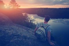 Homme occasionnel s'asseyant sur le bord de falaise au-dessus de la rivière et regardant loin Image libre de droits