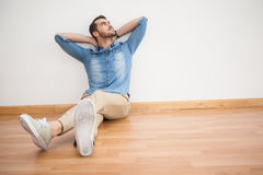 Homme occasionnel s'asseyant sur le plancher recherchant Images libres de droits