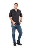 Homme occasionnel sûr dans la chemise et des jeans de plaid avec la main sur la ceinture regardant l'appareil-photo Photographie stock